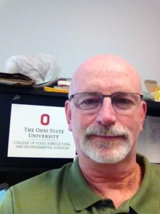 Jerry Iles smiling in his office in front of an OSU sign